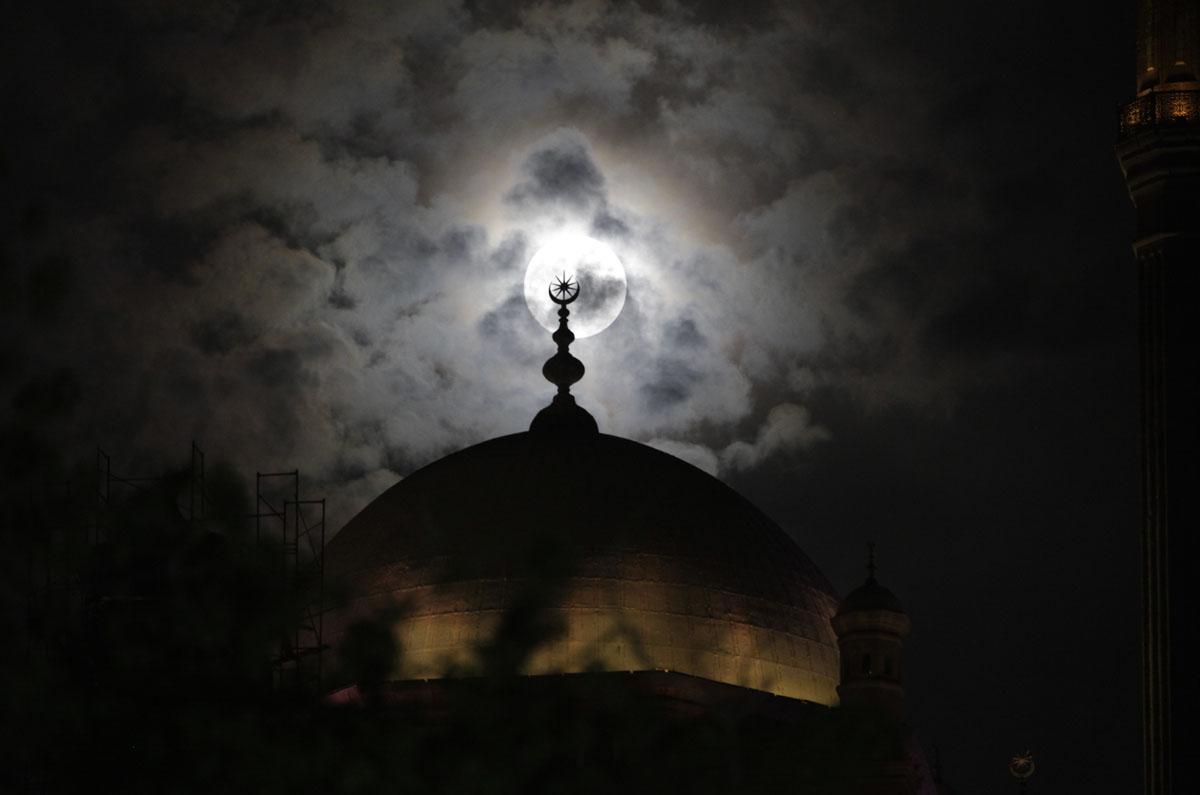 moon behind mosque